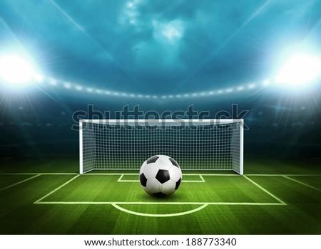 Soccer ball on green stadium, arena in night illuminated  - stock photo