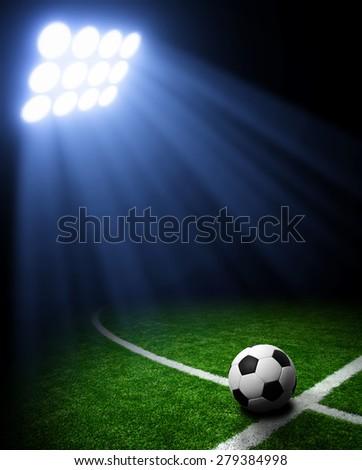 Soccer ball on green stadium, arena in night illuminated bright spotlights - stock photo