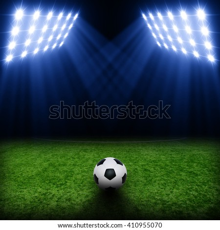 Soccer ball on green stadium, arena in night illuminated bright spotlights - stock photo
