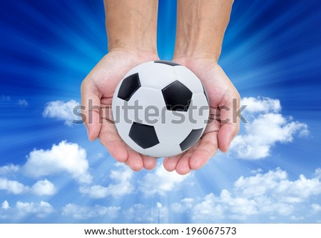 Soccer ball on hands isolated on blue sky  background