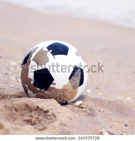 Soccer ball on sandy beach with retro filter - stock photo