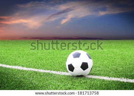 soccer ball on soccer field with sun set - stock photo