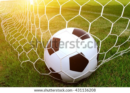 Soccer ball on the grass and have an orange light like the sun. - stock photo