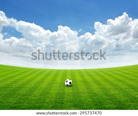 Soccer ball on the green field, Blue sky with cloud in summer, soft focus - stock photo