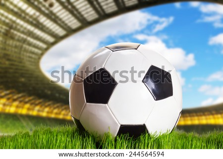 Soccer ball on the green stadium field - stock photo