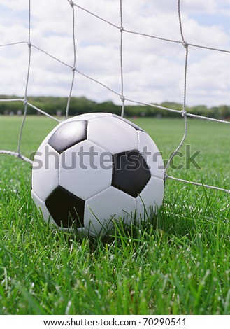 Soccer ball on the pitch field with goal in background - stock photo