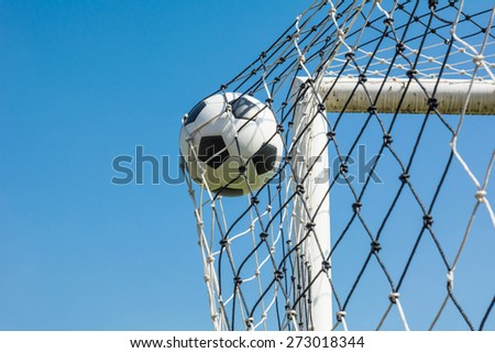 soccer ball shooting in goal net - stock photo