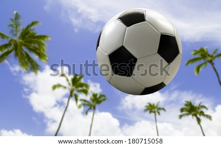 Soccer ball traveling on the beach - stock photo