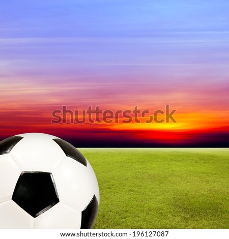 soccer ball with green grass field against sunset sky background