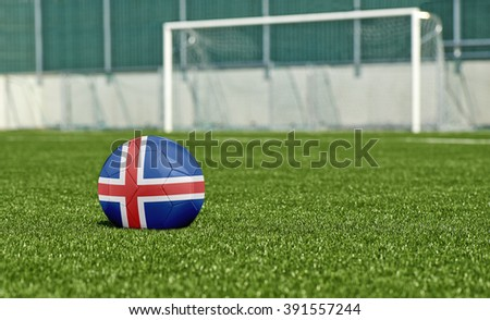 Soccer ball with the flag from Iceland; on the green field - stock photo