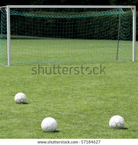 soccer balls in front of goal - stock photo