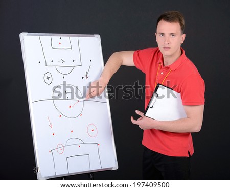 Soccer coach training with soccer men. Isolated on black background - stock photo