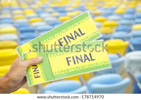 Soccer fan holding two Brazil final tickets in front of empty stadium seats - stock photo