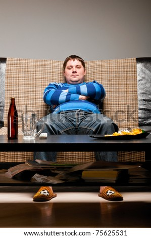 soccer fan is sitting on sofa with beer at home - stock photo