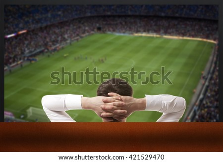 Soccer fan watching the TV - stock photo