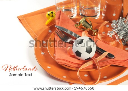Soccer football celebration party table setting with pates, cutlery, glasses, trophy, soccer ball and decorations in orange and white team colors with copy space. - stock photo