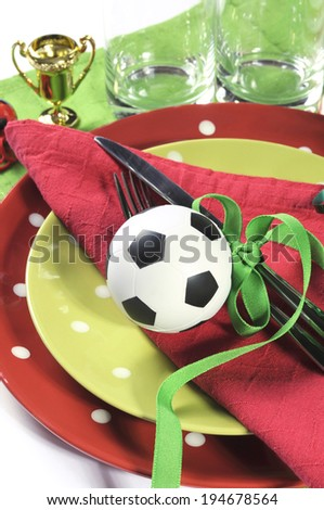Soccer football celebration party table setting with pates, cutlery, glasses, trophy, soccer ball and decorations in red white and green team colors. - stock photo