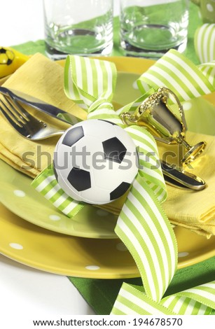 Soccer football celebration party table setting with pates, cutlery, glasses, trophy, soccer ball and decorations in yellow and green team colors. - stock photo