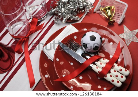 Soccer football celebration party table settings in red and white team colors. - stock photo