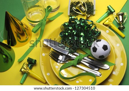 Soccer football celebration party table settings in yellow and green team colors. - stock photo