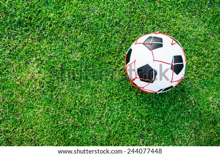 Soccer Football in a Net Mesh Sack Bag on Wide Grass Field with Natural Light (in Stadium or Local Field) Sport Concept and Idea / for background, wallpaper, texture. Standard Ball.