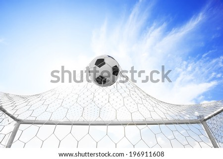 Soccer football in Goal net with Blue sky - stock photo