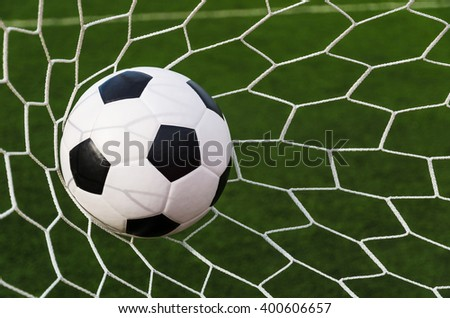 Soccer football in Goal net with green grass field.