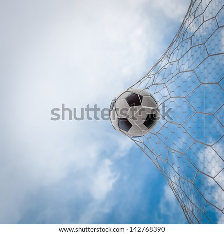Soccer football in Goal net with sky - stock photo