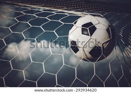 Soccer football in Goal net with sky field - stock photo