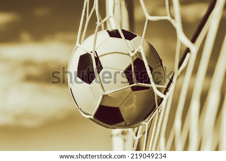 Soccer football in Goal net with sky field. BW Toned. - stock photo