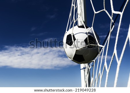 Soccer football in Goal net with sky field. Dark contrast - stock photo