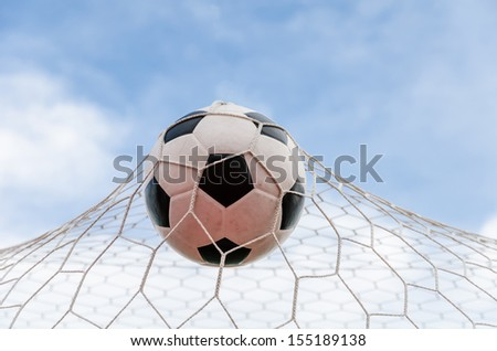 Soccer football in Goal net with the sky field. - stock photo