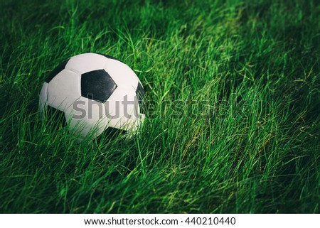 Soccer football on grass field, Soccer ball in fresh green summer or spring field grass, Film simulation - stock photo