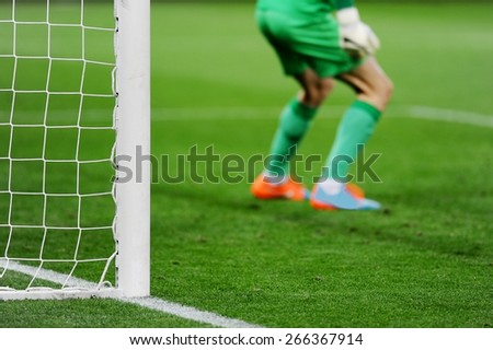 Soccer goal detail with goalkeeper preparing for a penalty kick in the background - stock photo