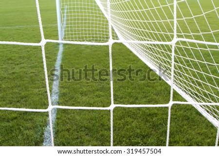Soccer goal net on green grass - stock photo