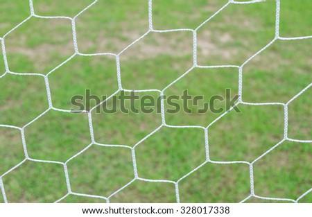 Soccer goal net on green grass background. - stock photo