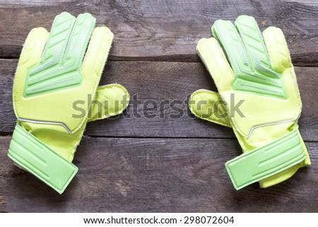 Soccer goalkeeper's gloves on wooden background - stock photo