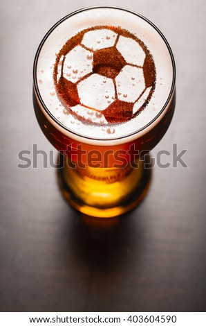 soccer or football ball symbol on foam in beer glass on black table, view from above - stock photo