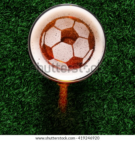 soccer or football ball symbol on foam of fresh lager beer glass on grass, view from above