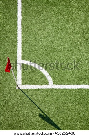 Soccer or football  field. White corner line against green ground and red color flag - stock photo