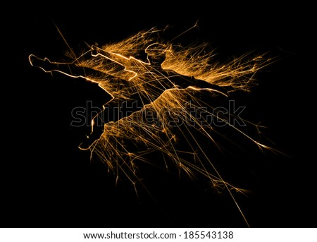Soccer or football player in mid air pose with sparks on black background and with copy space. - stock photo