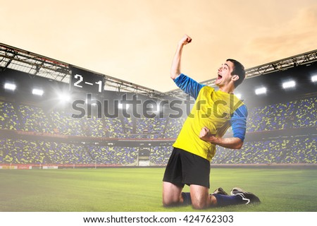 soccer or football player is celebrating goal on stadium