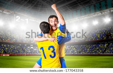 soccer or football players are celebrating goal on stadium - stock photo