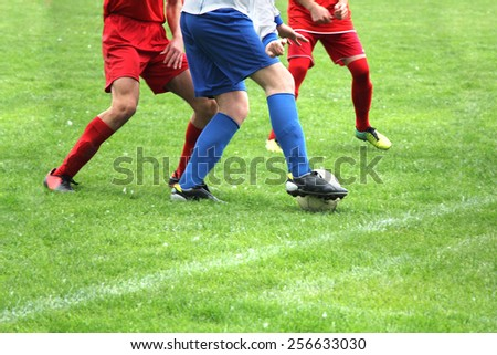 Soccer or football players in action on the field, blurred in motion  - stock photo