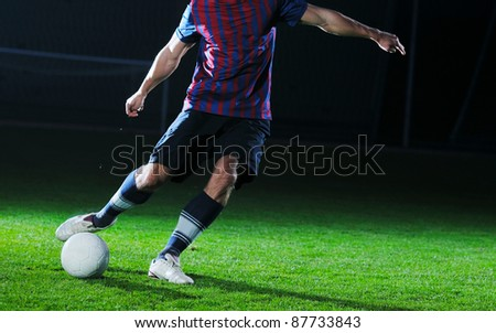 soccer player doing kick with ball on football stadium  field  isolated on black background  in night