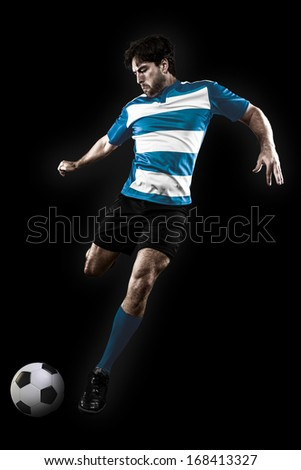 Soccer player in a Blue uniform kicking. Black Background