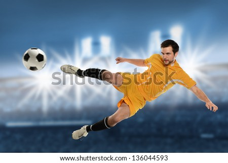 Soccer player in action kicking ball over stadium background
