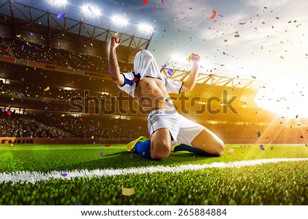 Soccer player in action on night stadium panorama background - stock photo