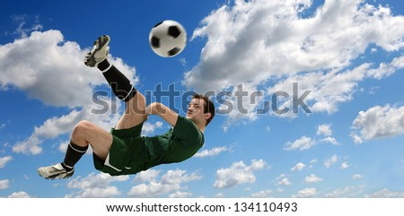 Soccer player kicking ball during sunny day