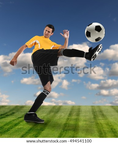 Soccer player kicking ball on grass field outdoors